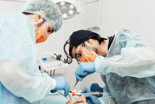 Two male dentists perform an operation on a patient. surgery in dentistry. professional uniform and equipment of a dentist. healthcare equipping a doctors workplace. dentistry Premium Photo