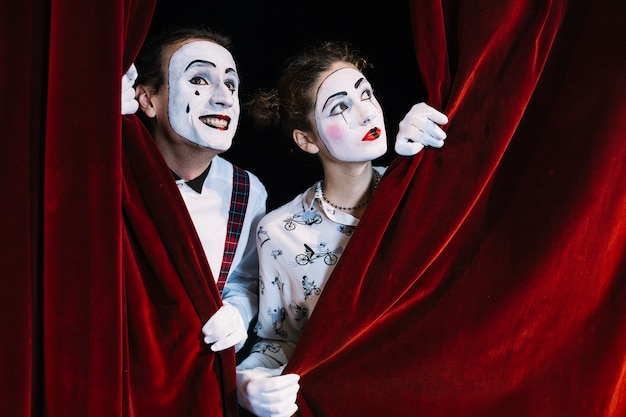 Two male and female mime artist looking through red curtain Free Photo