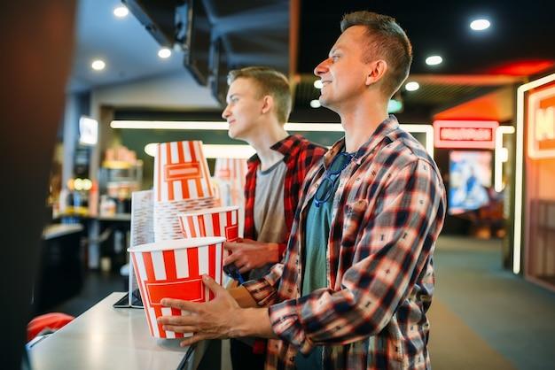 Двое друзей-мужчин покупают попкорн в кинотеатре перед началом сеанса. Premium Фотографии