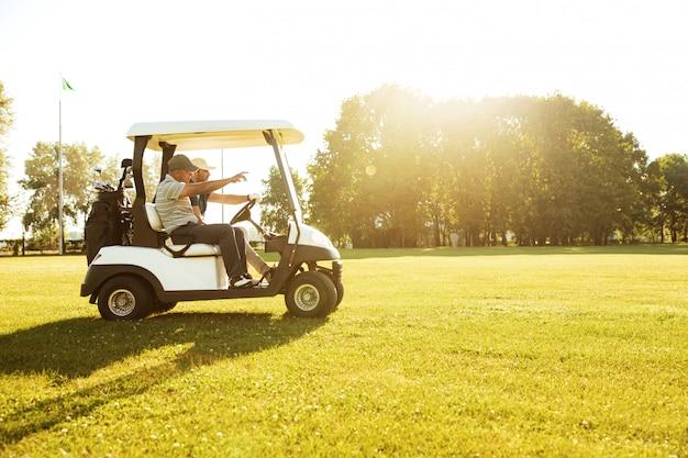골프 카트를 운전하는 두 남자 골퍼 무료 사진
