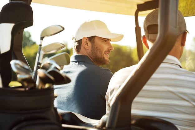 장바구니에 앉아 두 남자 골퍼 무료 사진