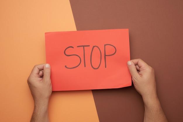 Две мужские руки держат красный лист с надписью стоп, вид сверху Premium Фотографии