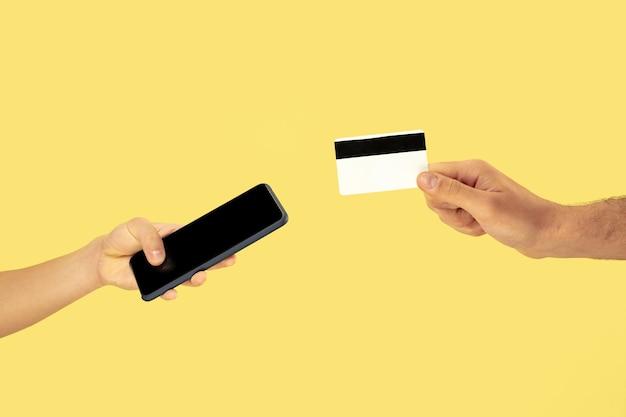 携帯電話またはスマートフォンとクレジットカードを保持している2つの男性の手 無料写真