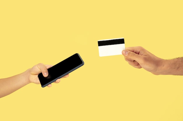 Two male hands holding cellphone or smartphone and credit card Free Photo