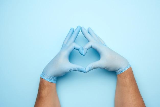 青いラテックス滅菌医療用手袋の2つの男性の手は、心臓のジェスチャー、善の概念、助けとボランティアを示しています Premium写真