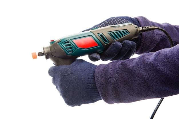 Две мужские руки в темно-синих защитных перчатках держат перфоратор Premium Фотографии