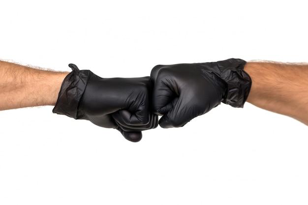 ゴム手袋をした男性の2つの手が握りこぶしで握られています。白い背景で隔離します。 2人の専門家間の対立の概念 Premium写真