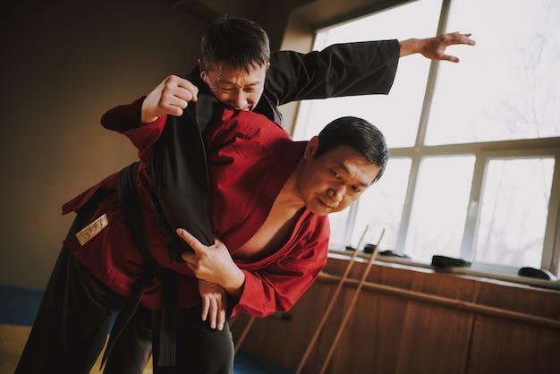 Two martial arts fighters in black and red kimono Premium Photo