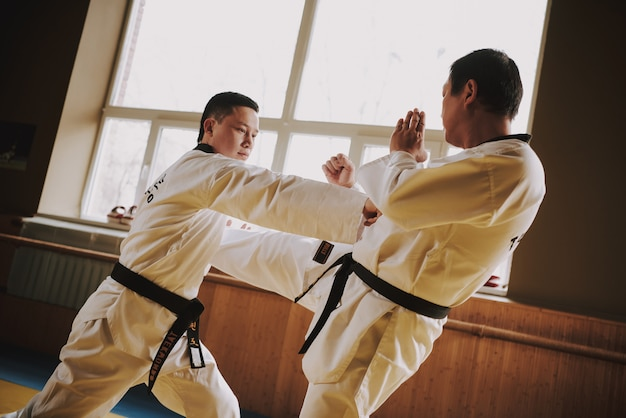 Two martial arts students in white sparring together. Premium Photo