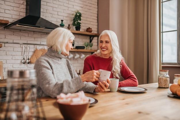 朝食時に話している2人の成熟した白髪のポジティブな女性 Premium写真