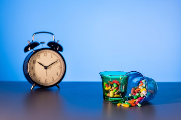 Two measuring cups with scattered medicines next to a vintage black alarm clock. the concept of the passing time. Premium Photo