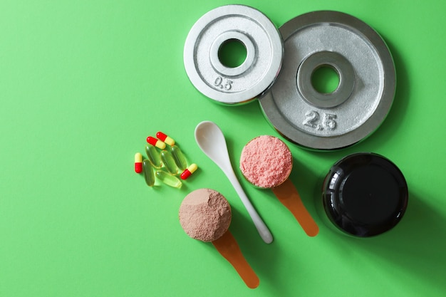 Two measuring spoons of whey protein and disks on table Premium Photo