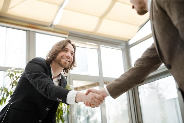 二人の男が握手してお互いを見つめている Premium写真
