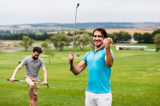 Two men having fun on golf course Free Photo