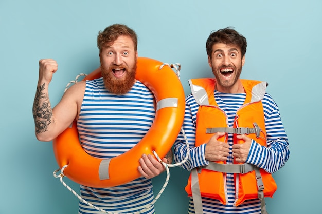 두 명의 인명 구조 원이 구명줄을 사용하고 특수 주황색 조끼를 입고 카메라를 즐겁게 바라 봅니다. 무료 사진