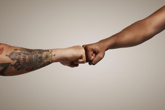 2人の男性、1人はタトゥーで薄い肌、もう1人は暗い肌で、白い壁に拳をぶつけます。 無料写真