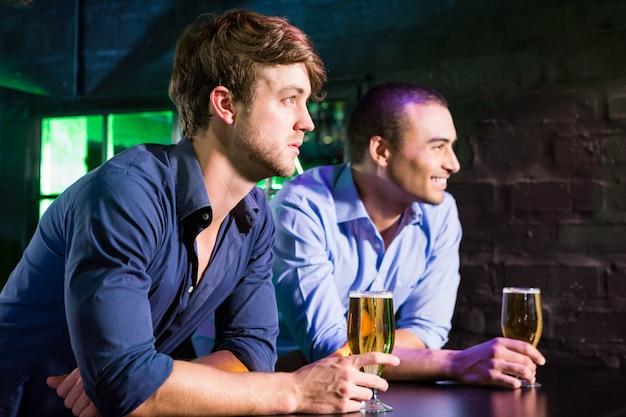 Two men smiling while having beer at bar counter in bar Premium Photo
