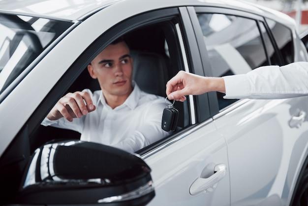 ショールームに車に対して2人の男性が立っています。車を顧客に販売するスーツを着たセールスマネージャーの拡大図。売り手は顧客に鍵を渡します。 無料写真