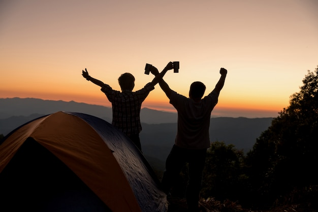 Two men tourists happy on the top of the mountain at near campfire Free Photo