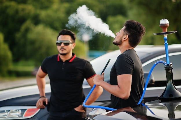 水ギセルを吸っているsuv車の近くでポーズをとっているすべての黒を身に着けている2人の男性 Premium写真