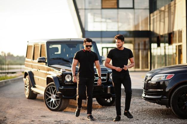Suvの車の近くでポーズをとるすべての黒を身に着けている2人の男性 Premium写真