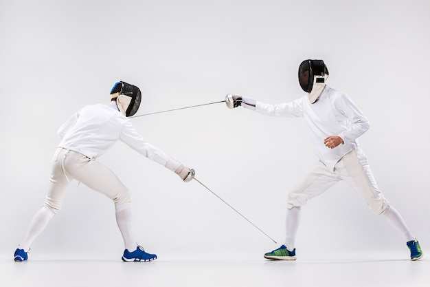 The two men wearing fencing suit practicing with sword against gray Free Photo