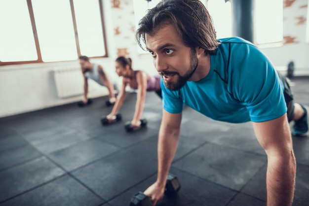 Two men and woman doing push ups on dumbbells. Premium Photo