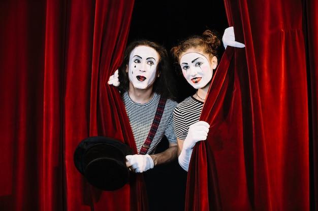 Two mime artist peeking through red curtain Free Photo