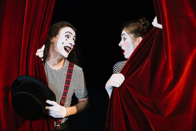 Two mime artist performing behind red curtain Free Photo