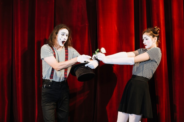 Two mime artist performing on stage in front of red curtain Free Photo