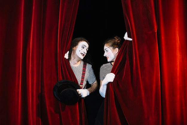 Two mime artist behind red curtain looking at each other Free Photo