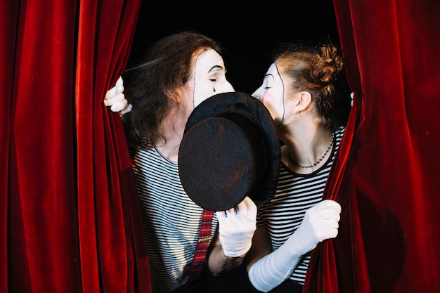 Two mime artist standing behind curtain kissing Free Photo