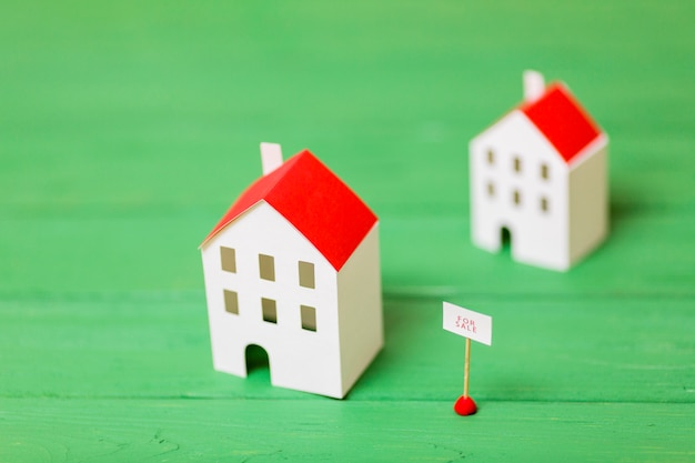 나무 녹색 책상에 판매를위한 두 개의 소형 집 모델 무료 사진