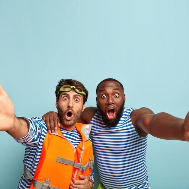 Due uomini di razza mista fissano con espressioni scioccate, fanno un selfie, si abbracciano, tengono le mascelle aperte, trascorrono il tempo libero in riva al mare Foto Gratuite