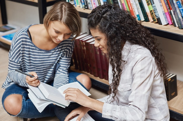 Еще две успешные многоэтнические студентки в повседневной одежде сидят на полу в университетской библиотеке Бесплатные Фотографии