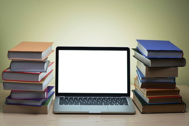 Two Mountains Of Books Next To A Laptop With Bright Screen