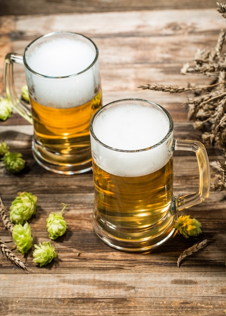 Two mugs of beer on wooden table with hops Premium Photo