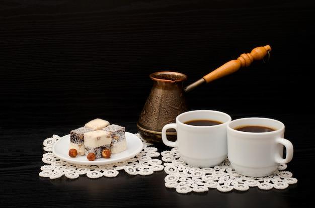 Two mugs of coffee, turkish lokum with hazelnut, cezve Premium Photo