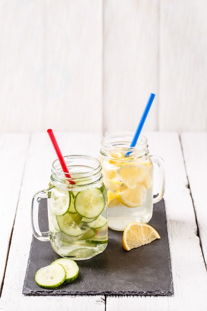Two mugs of infused detox diet refreshing waters: with cucumber and lemon Premium Photo