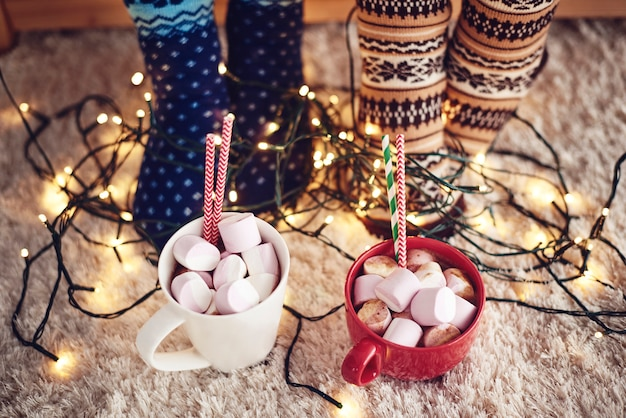 Two mugs with hot chocolate and marshmallow on rug Free Photo
