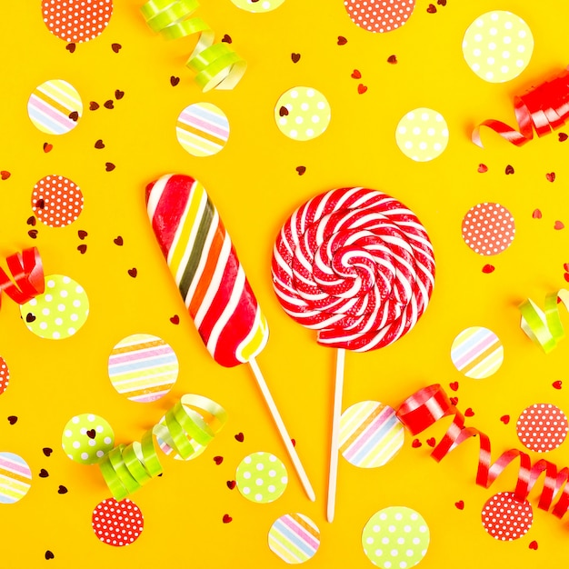Two multicolored candies among paper circles of confetti, glitter and festive ribbons Premium Photo