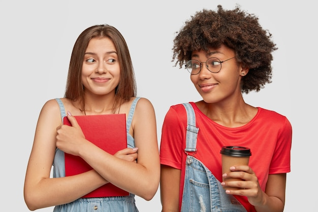 Two multiethnic females college students have happy expressions after having classes, drink takeaway coffee, hold book, prepare for exams together, have truthful friendship. people, youth, studying Free Photo