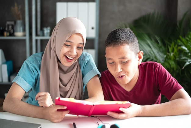 Two muslim students reading book together Premium Photo
