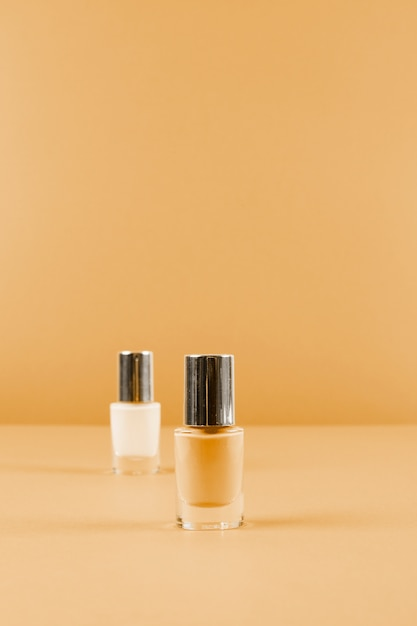 Two nail polish bottles on abstract brown background Free Photo