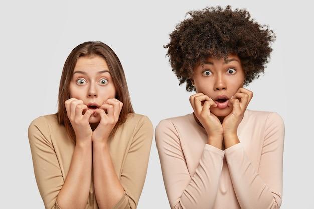 2人の神経質な混血の女性は心配そうに見え、驚きと恐怖を感じ、開いた口の近くに手を保ち、虫の目で見つめ、白い壁に向かってポーズをとります。否定的な感情の概念 無料写真
