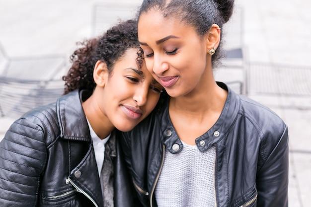 Два североафриканских друга-подростка сидят вместе и разговаривают Premium Фотографии