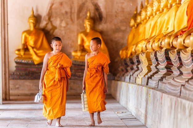 Two novices walking and talking in old temple at ayutthaya province, thailand Premium Photo