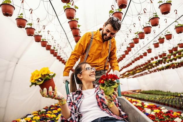 楽しい2つの保育園の庭の労働者。女性がそれに座っていると花が付いている鍋を保持しながら手押し車を押す男。周りは色とりどりの花でいっぱいです。 Premium写真