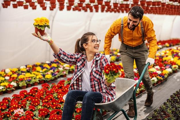 楽しい2つの保育園の庭の労働者。女性がそれに座っていると花が付いている鍋を保持しながら手押し車を押す男。 Premium写真