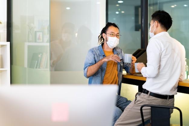 ソーシャルディスタンスプラクティスオフィスでコーヒーが休憩しながら話している2人のサラリーマン。彼らはフェイスマスクを着用し、新しい通常のライフスタイルとしてcovid-19コロナウイルス感染のリスクを減らします。 Premium写真